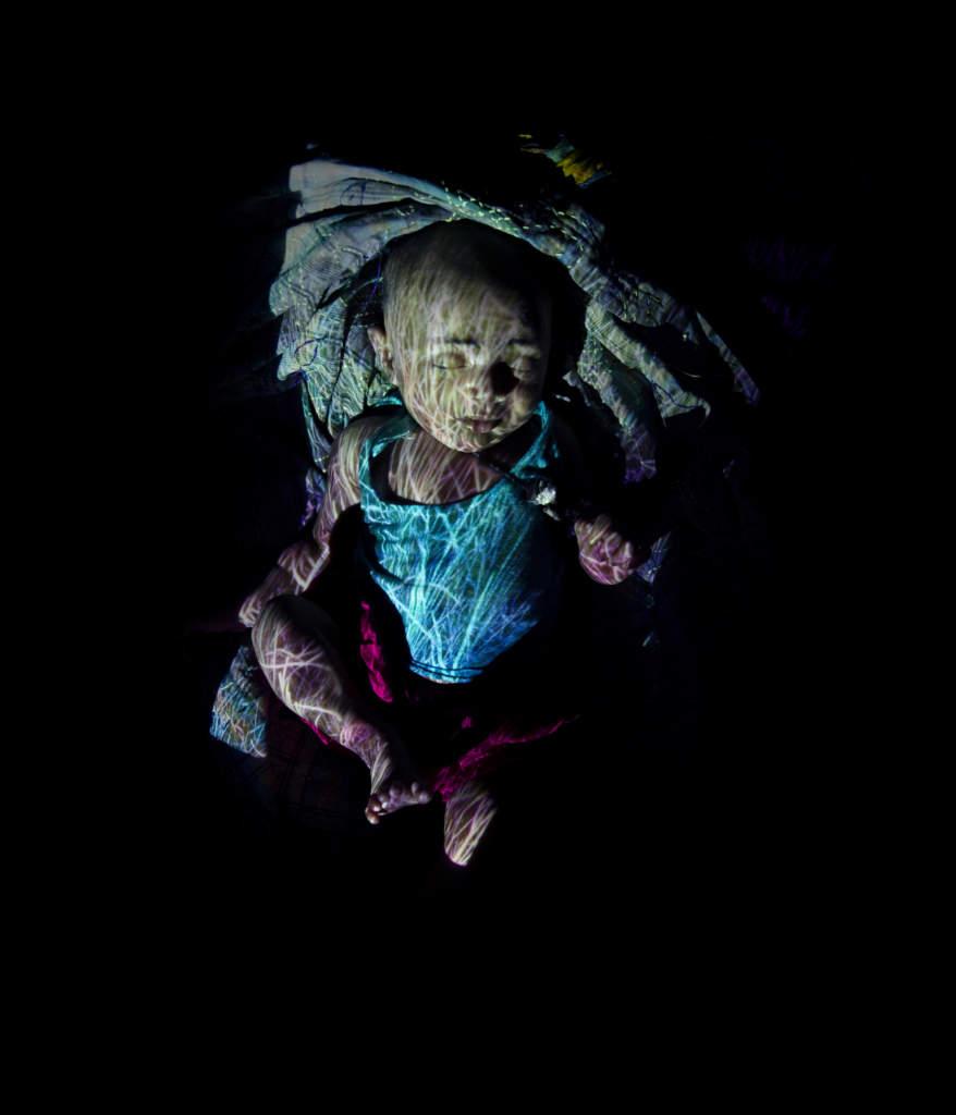 Namnlös flicka, 7 dagar.  Hon har inget namn, men än så länge ett hem. Den här lilla flickan i Bhola i södra Bangladesh föddes mitt i en översvämning. Den här gången nådde vattnet inte upp till familjens hus. Men hur blir det nästa gång.  Redan om några decennier kommer 17 procent av Bangladeshs landyta att ligga under vatten. Då, om inte förr, kommer den här flickan att tvingas på flykt från sitt barndomshem. Det är inte spekulation. Det är fakta.