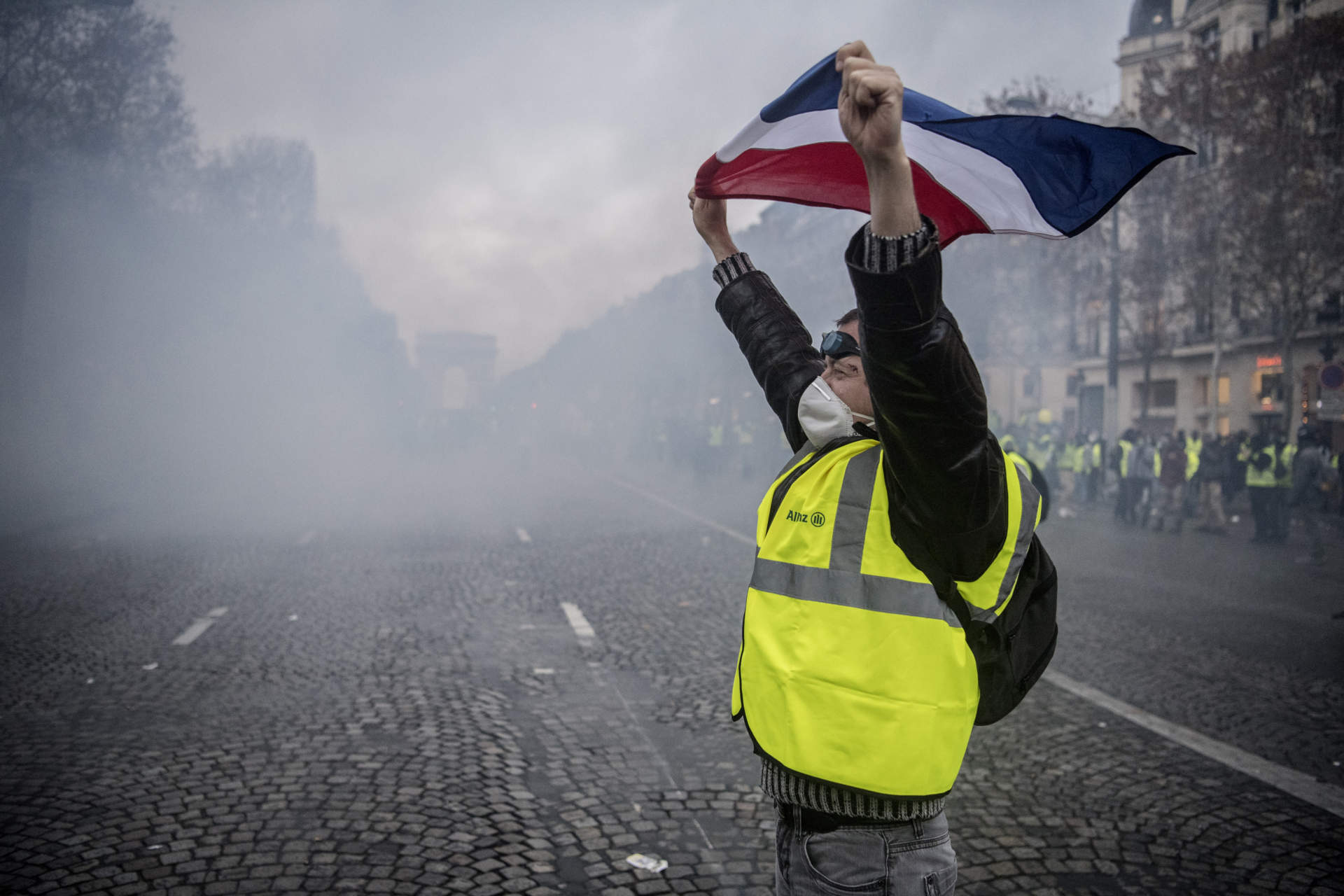Mitt i tumultet ställde sig en man framför poliserna i tystnad med den franska flaggan sträckt över huvudet.